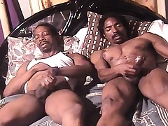 Two sexy and horny dark skinned studs masturbate together on the moulding